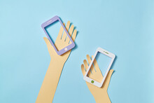 Two Papercraft Hands With Smartphone Frames.