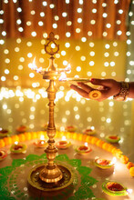 Woman's Hand Lighting Oil Lamps During Diwali