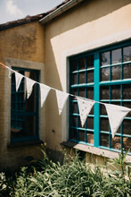 Summer House With Blue Windows And Fluttering Bunting