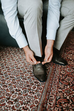 Middle Aged Man In Suit Tying His Shoe Strings