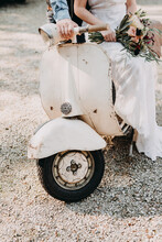 Bride And Groom Sitting On An Antique White Vespa