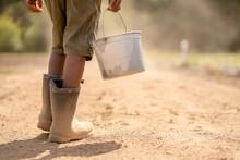 Boy Holding Bucket On Farm Road