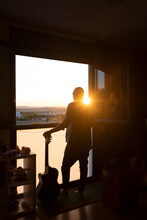Young Man Posing Besides A Window With Acoustic Guitar At Home At Sunset