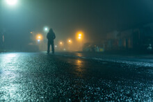 A Low Angle Of A Hooded Figure Standing In A Street At Night
