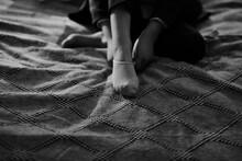 Monochrome Image Of Someone Putting On Socks