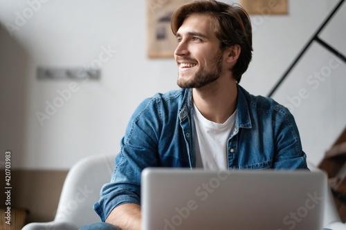 Successful entrepreneur smiling in satisfaction as he checks information on his laptop computer while working