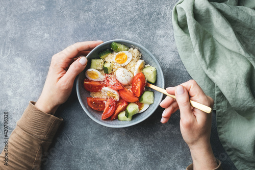 Female hands holding cous cous salad bowl with cucumber, cherry tomato and quail eggs Fotobehang