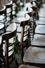 Empty Wooden Chairs In Rows Decorated For Christmas With Pine Leaves And Bow