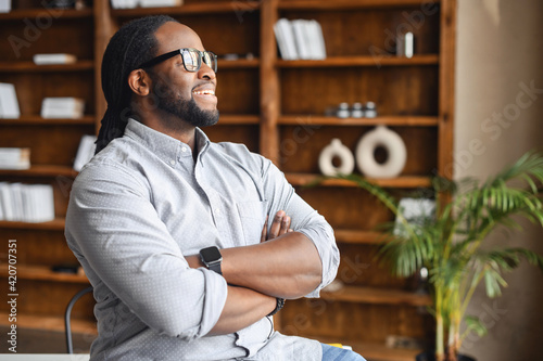 I made this. Portrait of ambitious confident black leader, ceo, standing with arms crossed on chest at office of successful profitable company, looking away, proud of his achievement career wellbeing