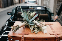 Ready To Leave The Wedding With A Wedding Bouquet & Suitcase In The Car