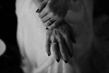 Monochrome Image Of Bride Holding Hands On Knees