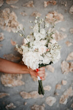 Close Up Of White Wedding Bouquet In Front Of Stone Wall