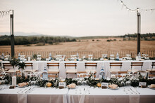 Outdoor Wedding Reception With White Bunting Flags And String Lights And View On Spanish Landscape
