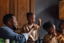 Family Time - A Father Feeding His Daughter In A Restaurant