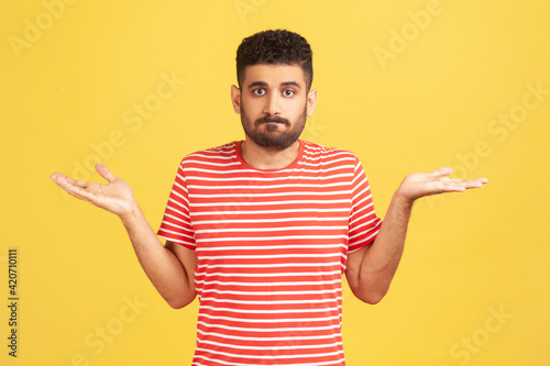Fotografia, Obraz Puzzled clueless man with beard in striped red t-shirt spreading hands and shrugging shoulders, not sure and indifferent in some questions