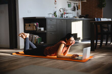 Brunette Woman On Yoga Mat Using Laptop At Home