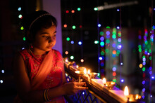 Little Girl Igniting Oil Lamps During Diwali