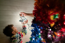 Excited Girl Takes String Of Christmas Lights From Father