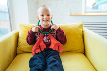 Laughing Little Boy In A Christmas Sweater Trying On Toy Antlers