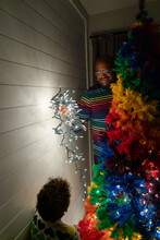 Father And Daughter Put Lights On A Tree