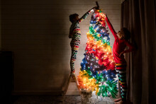 Siblings Decorate A Rainbow Christmas Tree