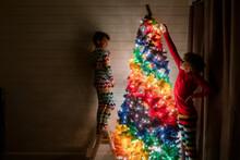 Siblings Decorate Tree In Dark Room
