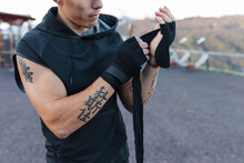 Crop Tattooed Sportsman Bandaging Hands On Sports Ground