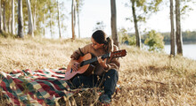 Young Woman Playing The Guitar Outside