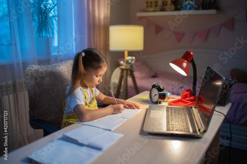 Schoolgirl girl studies online on a laptop at home.