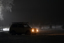 Car With Glowing Headlights In Night Countryside
