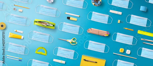 Obraz Flat lay top view of face mask and school supplies, back to school and coronavirus concept. - fototapety do salonu