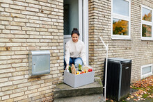 Woman Picking Up A Grocery Delivery At Her Door