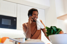 Man Talking On A Phone While Preparing Dinner