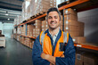 Leinwandbild Motiv Smiling portrait of a male supervisor standing in warehouse with his arm crossed looking at camera