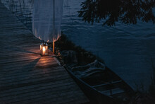 Rowboat On A Lake With Candle Light At Dawn