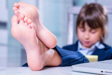Humorous Portrait Of Cute Little Business Child Girl With Bare Feet Works With Laptop. Selective Focus On Bare Feet.