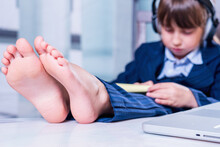 Humorous Portrait Of Cute Little Business Child Girl With Bare Feet Works Remotely With Laptop. Selective Focus On Bare Feet.