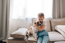A Little Girl With A Dog At Home.