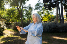 Grey Hair Mature Woman Practicing Tai Chi In The City Park