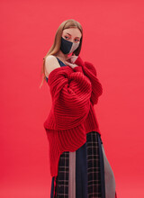 Model In Mask Posing By Red Background