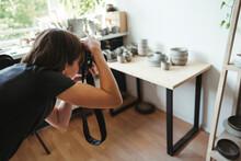 Female Artisan Photographs Ceramic Products.