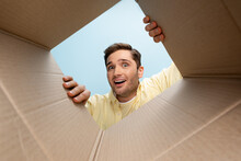 Bottom View Of Curious Man Looking At Camera From Carton Box Isolated On Blue