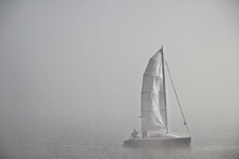 Unidentifiable Man On The Boat In The Mist And Fog On The Lake,