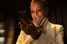 Senior Business Woman Smiling And Taking Off The Mask While Using Her Phone At Night