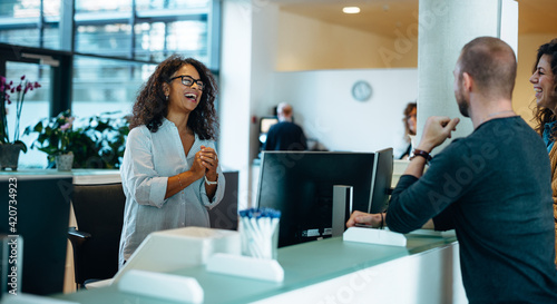 Valokuva Smiling receptionist assisting people at municipal office
