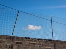 Cloud Enclosed Behind A Metal Fence.