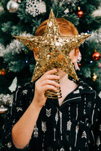 Holding Christmas Tree Star Decoration Over Face
