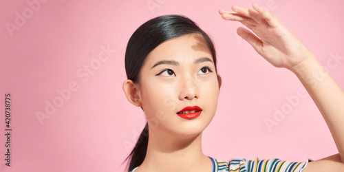 Fototapeta Young beautiful Asian woman scared of sunshine isolated over pink background. Concept for summer skin care and skin protection from uv sunshine obraz
