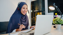 Asia Muslim Lady Wear Headphone Watch Webinar Listen Online Course Communicate By Conference Video Call At Night Home Office. Remotely Working From House, Social Distance, Quarantine For Corona Virus.