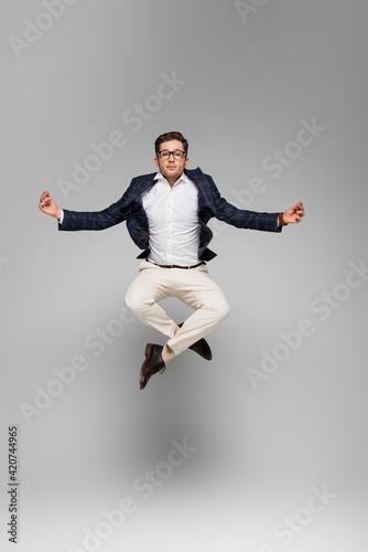 Obraz full length of businessman in glasses meditating and levitating on grey - fototapety do salonu